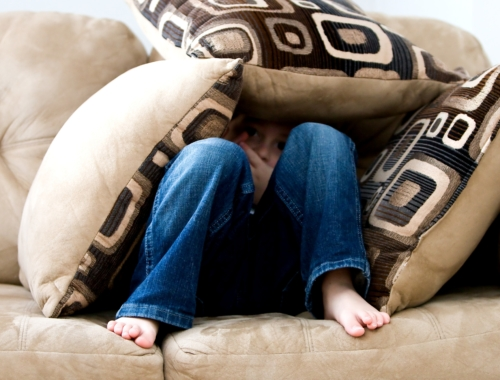 Child hiding in couch cushions
