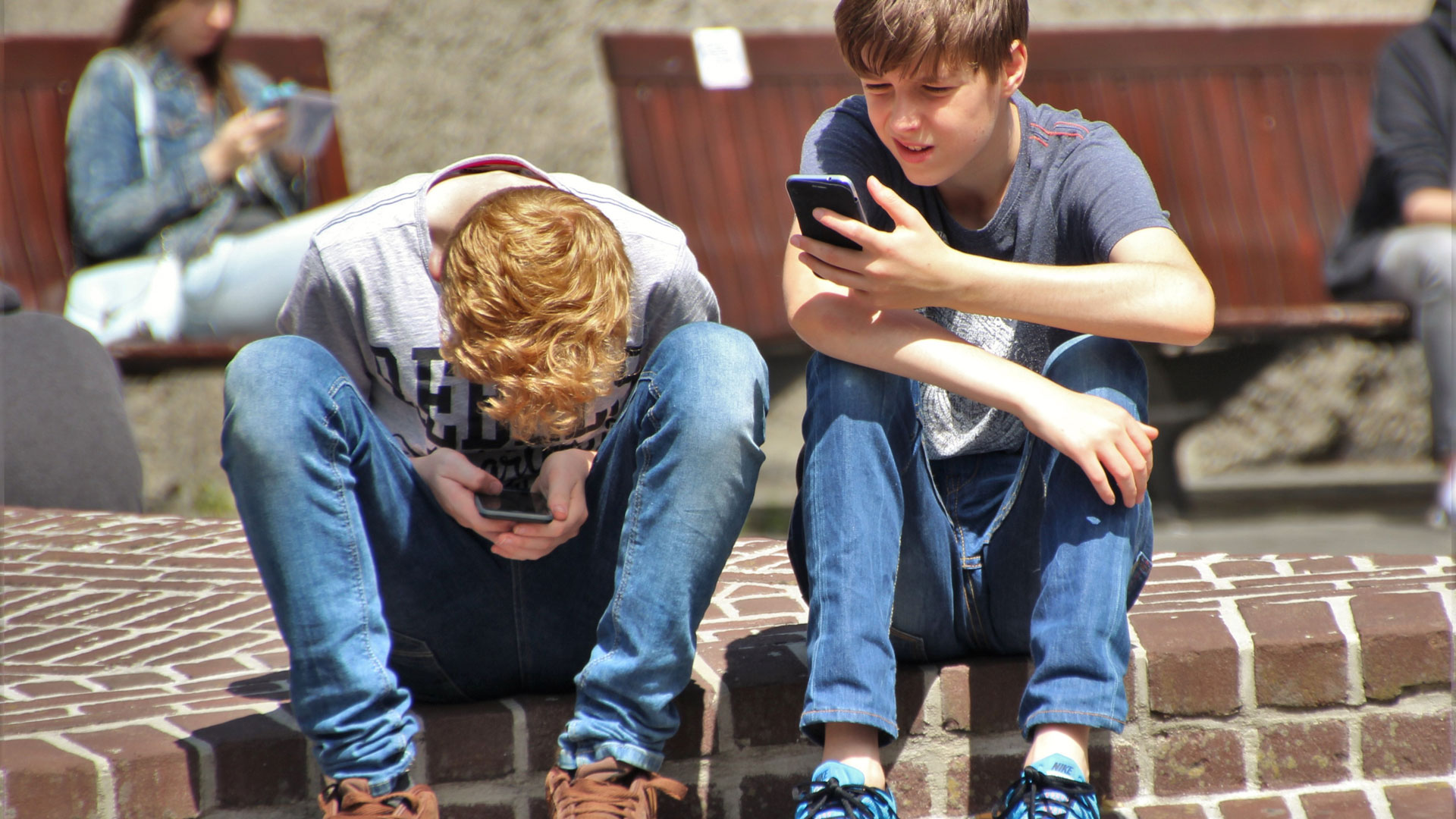 Two teenage boys look at their mobile phones