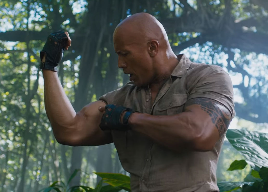 The Rock checks out his own muscles in Jumanji: Welcome To The Jungle.