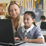Young-School-Girl-on-Laptop-with-Teacher1440