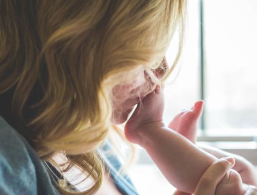 Mum kisses baby's foot.