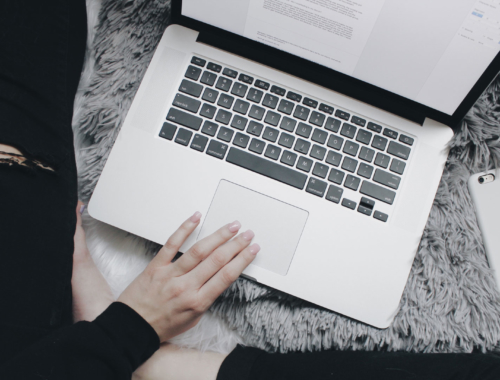 Laptop and phone on bed with woman