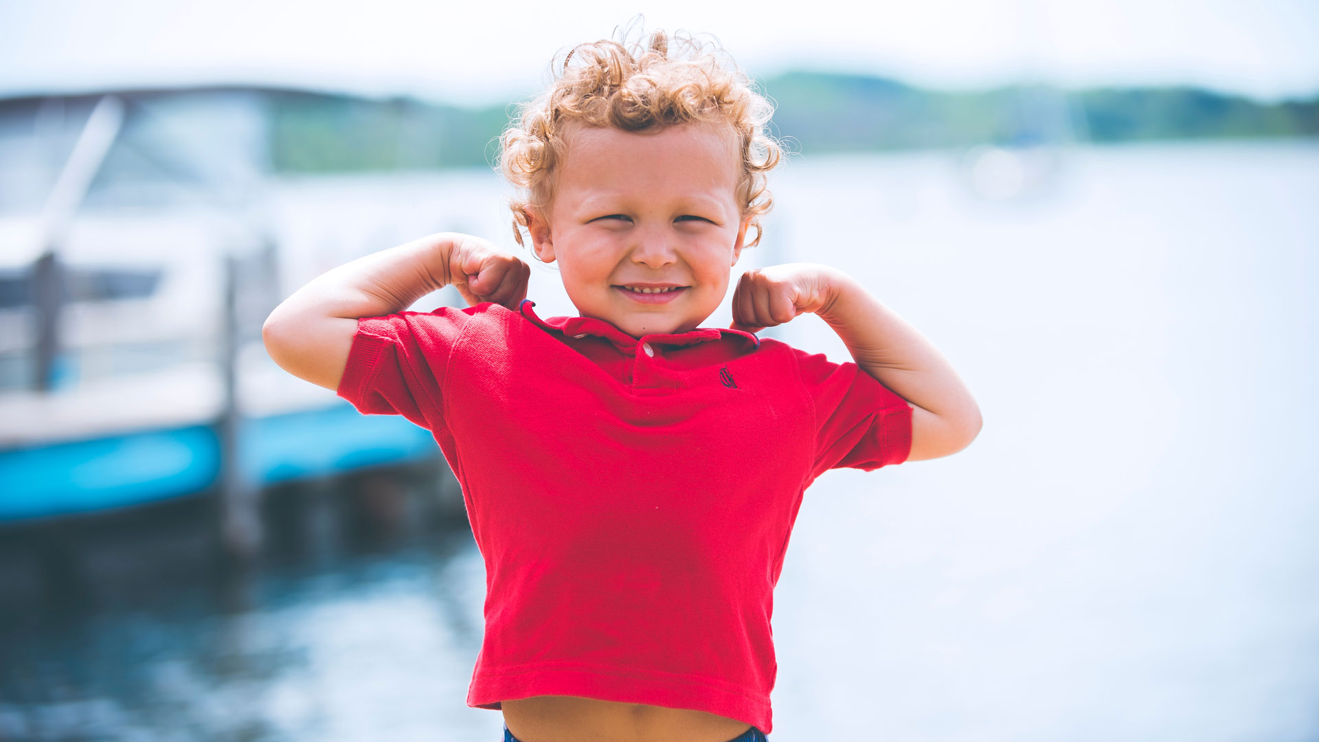 Boy in a red shirt flexing his arms