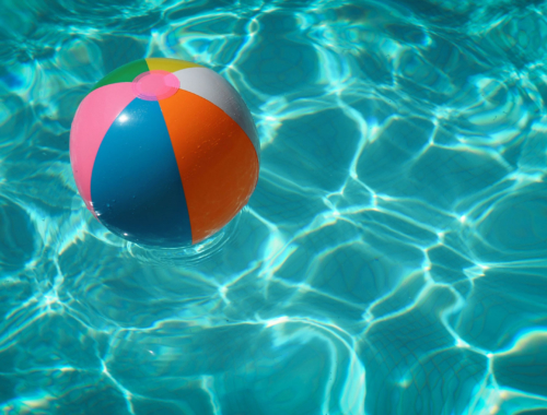 A rainbow beachball floating in a blue swimming pool.