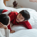 mother-tween-son-on-bed-laughing2160