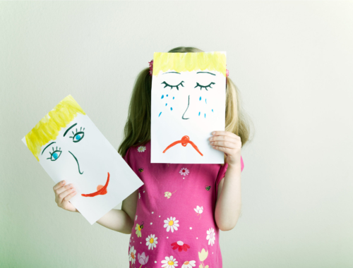 girl-holding-sad-happy-face2160