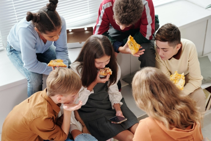 teens-eating-pizza-with-one-on-phone2160