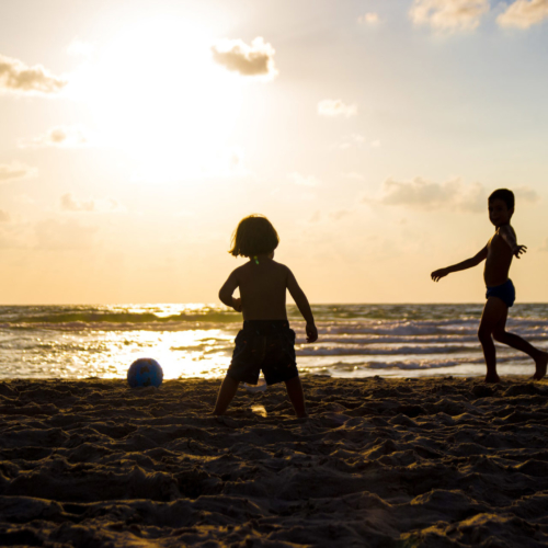 kids-playing-on-the-beach-in-sillouette
