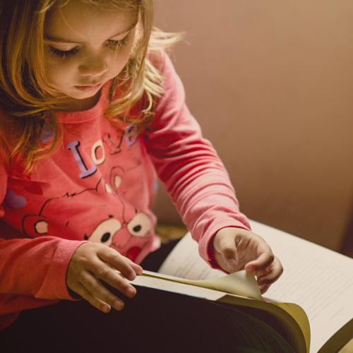 young-girl-looking-through-a-book2160